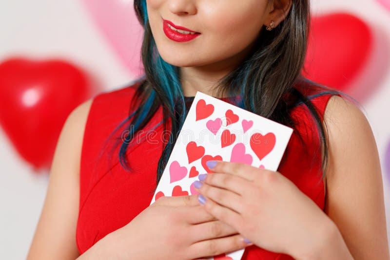 Uma jovem mulher bonita toma um cartão com corações com uma declaração do amor Dia do `s do Valentim foto de stock