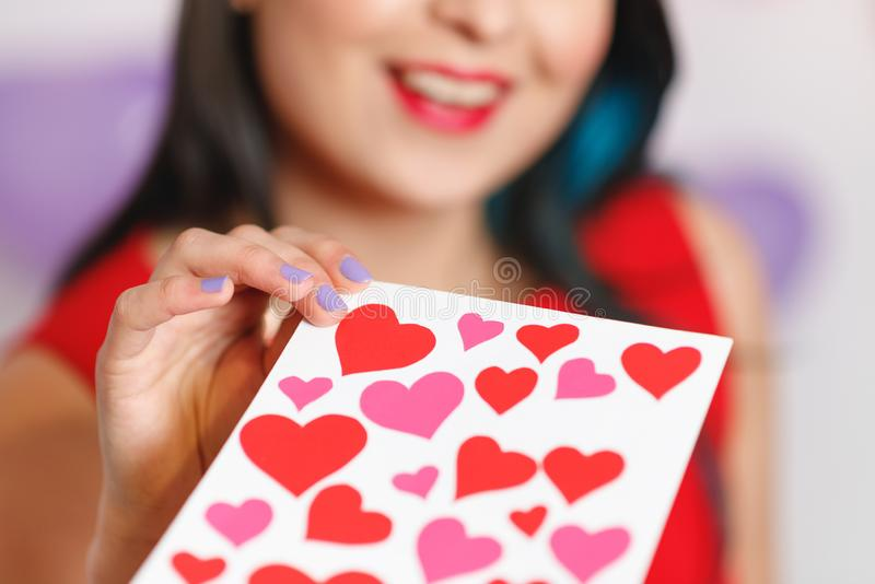 Uma jovem mulher bonita toma um cartão com corações com uma declaração do amor Dia do `s do Valentim imagens de stock royalty free