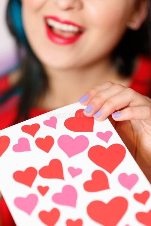 Uma jovem mulher bonita toma um cartão com corações com uma declaração do amor Dia do `s do Valentim imagem de stock