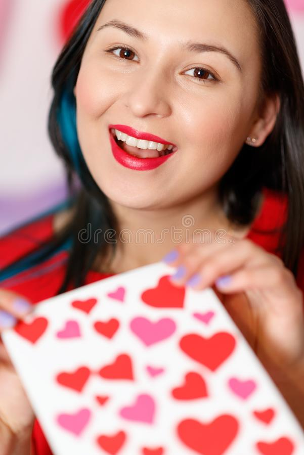 Uma jovem mulher bonita toma um cartão com corações com uma declaração do amor Dia do `s do Valentim foto de stock royalty free