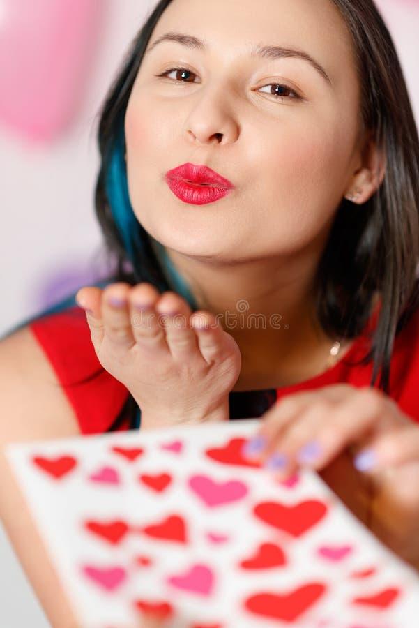 Uma jovem mulher bonita toma um cartão com corações com uma declaração do amor Dia do `s do Valentim imagens de stock