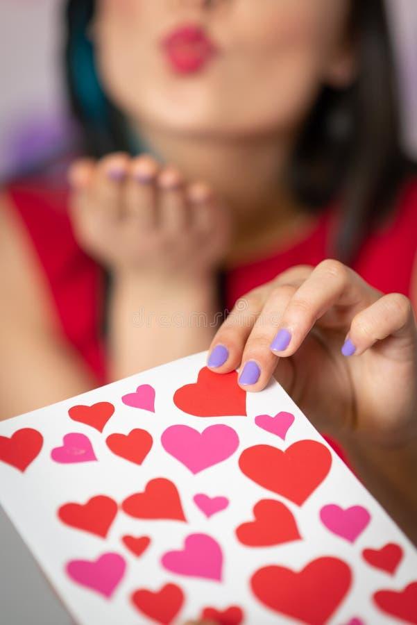 Uma jovem mulher bonita toma um cartão com corações com uma declaração do amor Dia do `s do Valentim imagem de stock royalty free