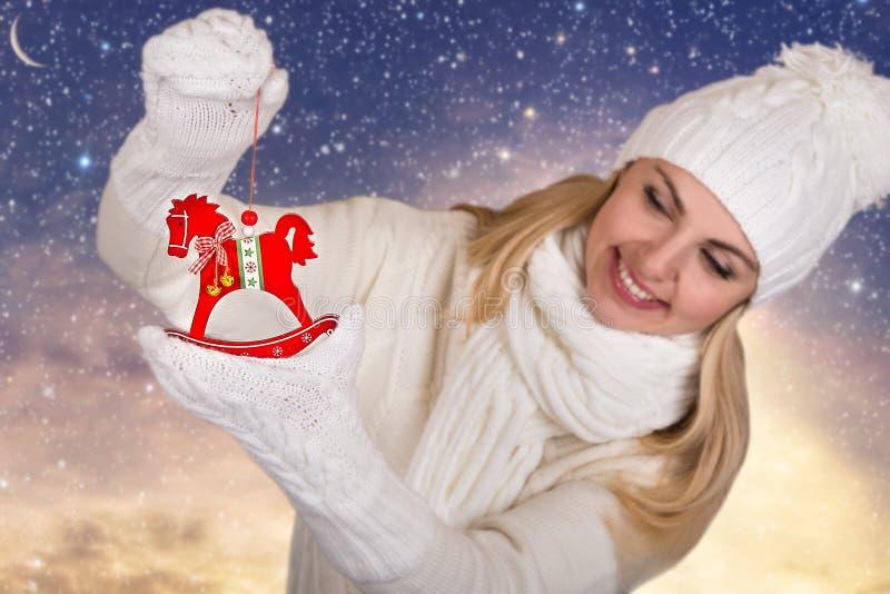 Uma jovem mulher branco bonito na roupa feita malha está guardando a decoração de madeira do Natal do cavalo para a árvore de Nat foto de stock royalty free