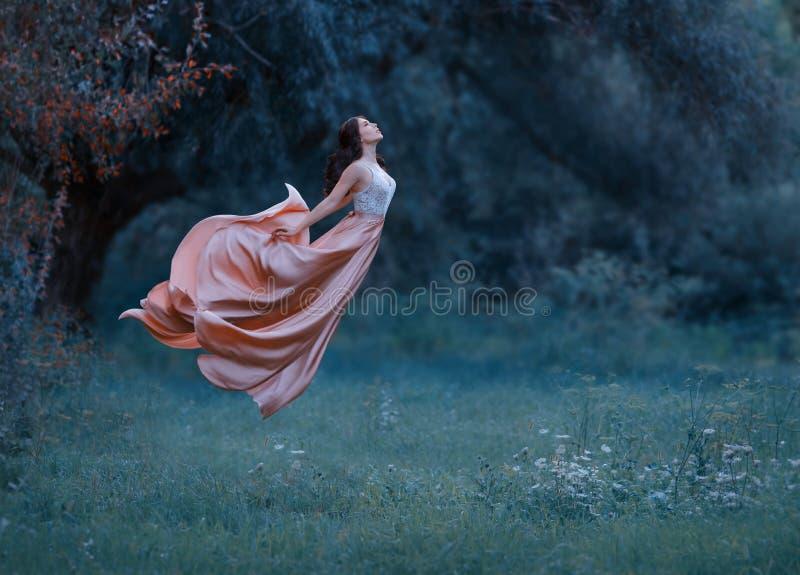 Uma jovem mulher, uma bruxa misteriosa está flutuando no ar como uma borboleta Um vestido luxuoso, longo vibra no vento foto de stock