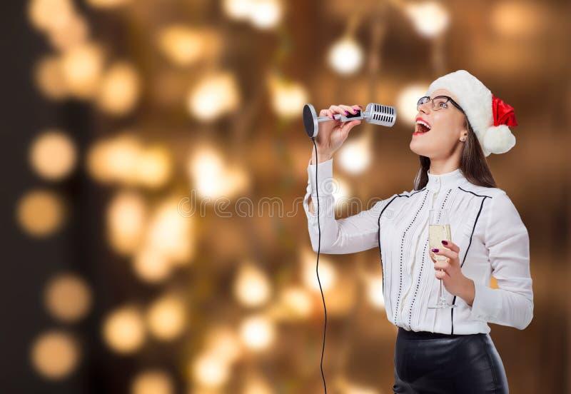 Uma jovem mulher canta em um microfone do karaoke fotos de stock