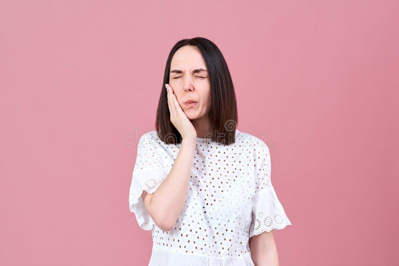 Uma jovem mulher com cabelo escuro parafusou acima seus olhos, põe sua mão a seu mordente devido a uma dor de dente severa foto de stock