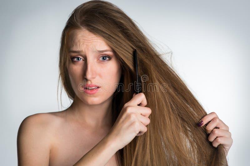 Uma jovem mulher com cabelo longo não pode pentear seu cabelo imagem de stock royalty free