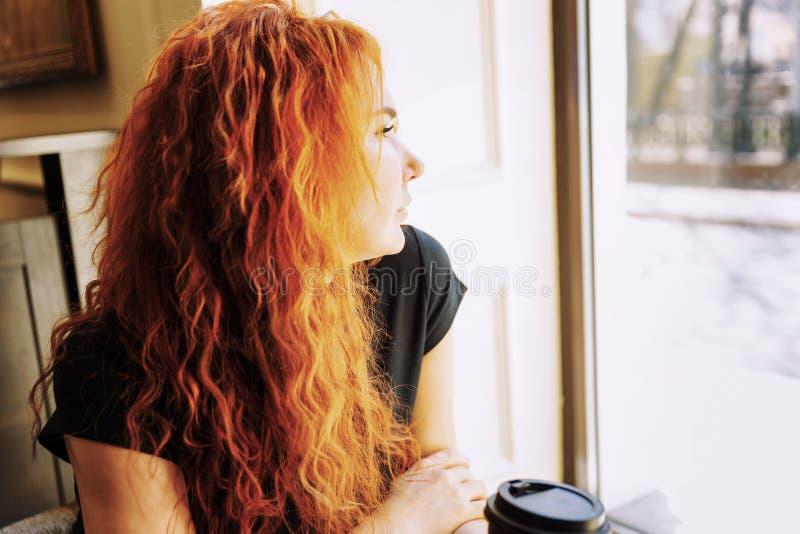 Uma jovem mulher com cabelo vermelho brilhante senta-se em um caf? e olha-se para fora a janela Solid?o na cidade imagens de stock royalty free