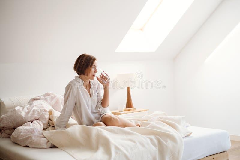 Uma jovem mulher com a camisa da noite que senta-se dentro na cama na manhã, água potável imagem de stock