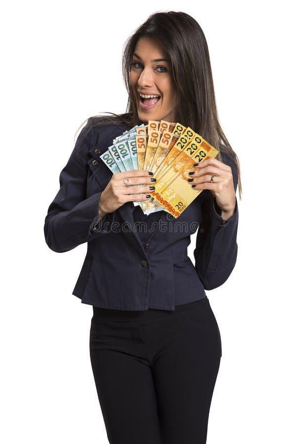 Uma jovem mulher com dinheiro real em suas mãos imagem de stock