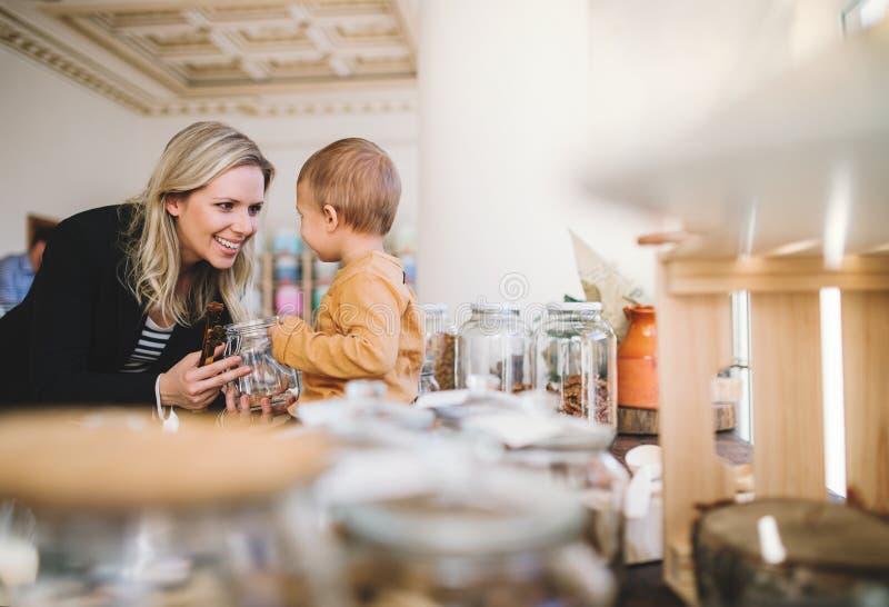 Uma jovem mulher com os mantimentos de compra de um menino da criança na loja zero do desperdício fotografia de stock