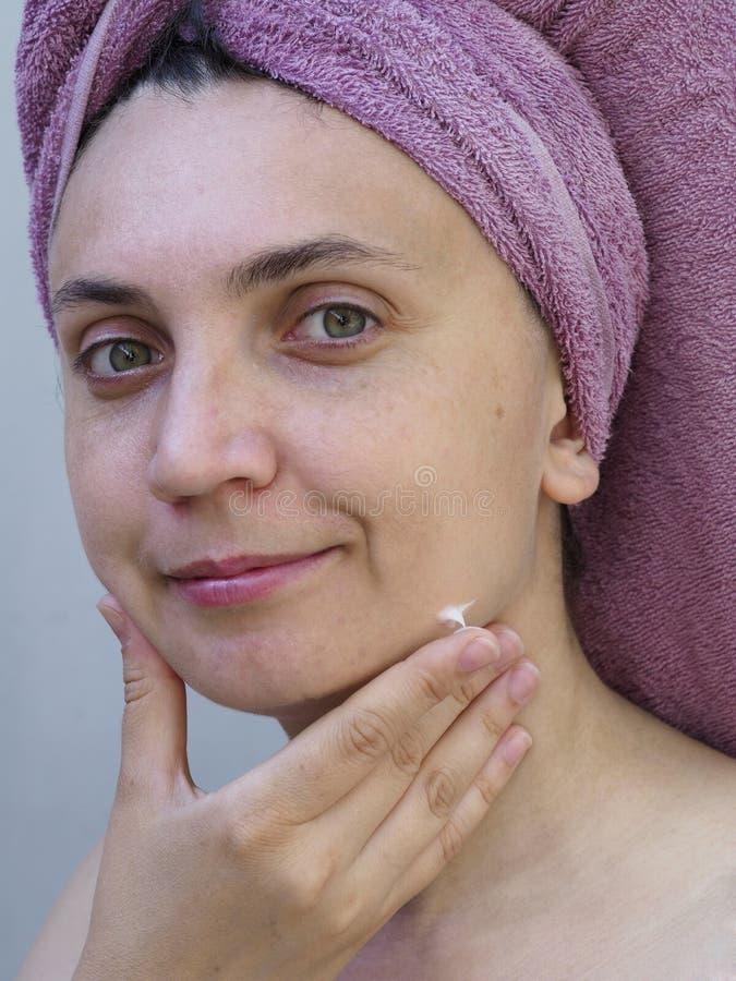Uma jovem mulher com uma toalha em seus sorrisos e cursos principais a pele de sua cara fotos de stock royalty free