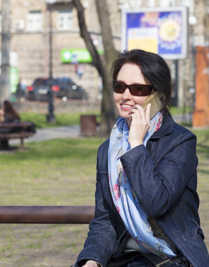 Uma jovem mulher com um humor alegre comunica-se em um smartphone em um parque da mola imagens de stock royalty free