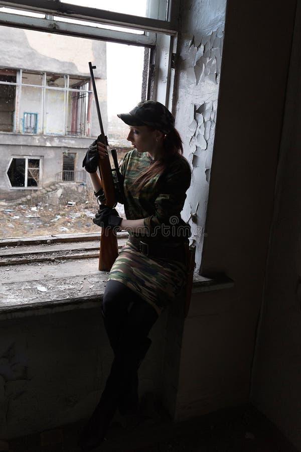 Uma jovem mulher com um rifle no uniforme na janela que olha a rua O atirador furtivo da mulher em um terno e em um tampão verdes fotos de stock royalty free