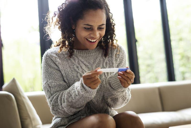 Uma jovem mulher com um teste de gravidez imagens de stock