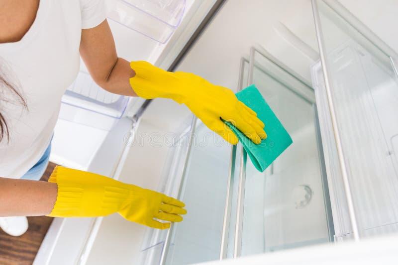 Uma jovem mulher de uma empresa de limpeza profissional limpa em casa Um homem lava a cozinha lava o refrigerador dentro imagens de stock royalty free