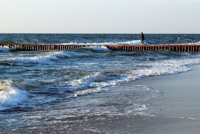 Uma jovem mulher desconhecida que anda ao longo do quebra-mar alemão velho t imagens de stock
