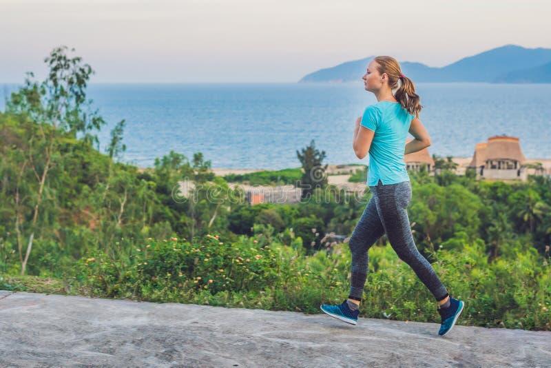 Uma jovem mulher desportivo é contratada na corrida contra o mar fotos de stock royalty free