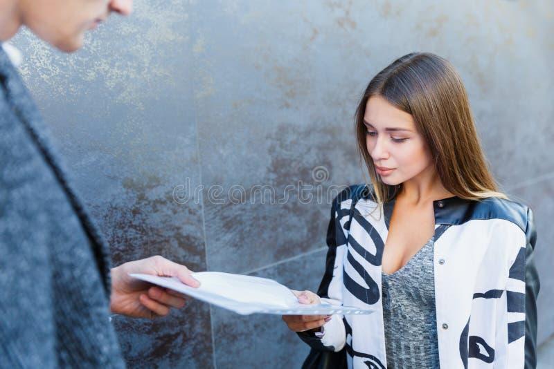 Uma jovem mulher do negócio cede um original a um homem imagem de stock