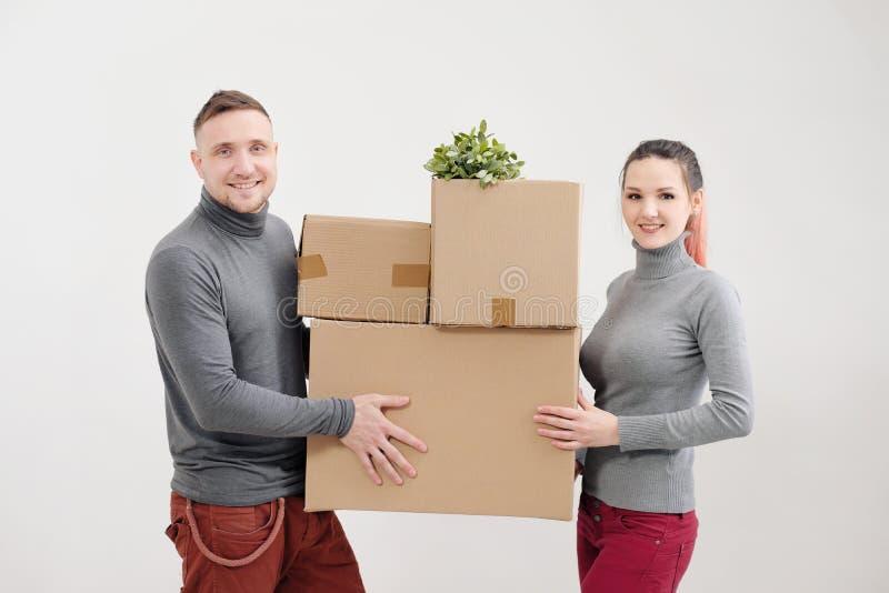 Uma jovem mulher e um homem levam caixas de cartão pesadas com coisas Apartamento claro branco Riem e beijam imagem de stock royalty free