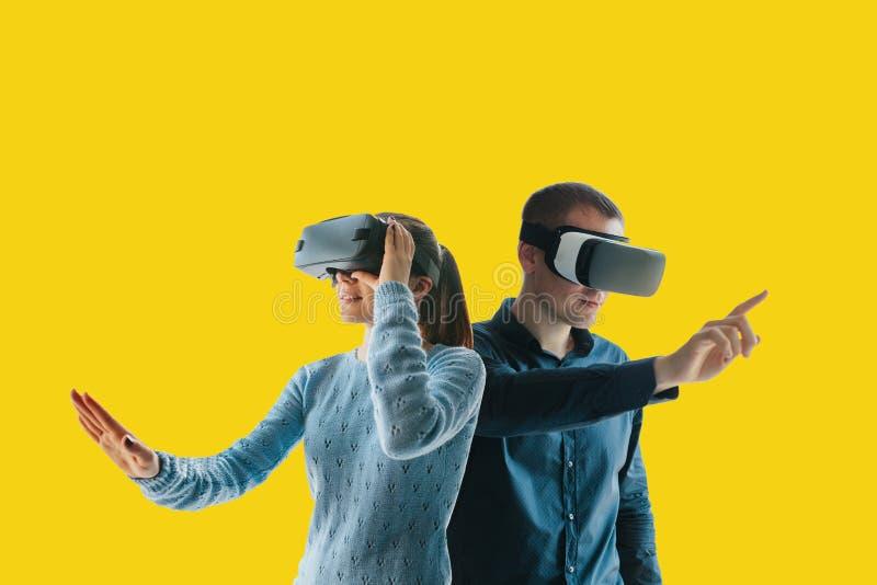 Uma jovem mulher e um homem novo em vidros da realidade virtual O conceito de tecnologias modernas e de tecnologias do fotos de stock royalty free