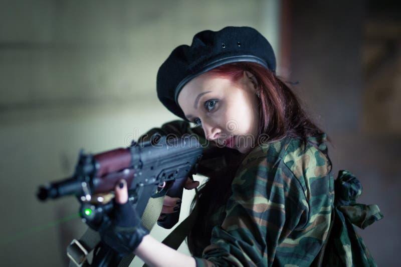 Uma jovem mulher em uma construção abandonada com uma arma Vista do laser na máquina Apontar da máquina com um laser A menina den fotografia de stock royalty free