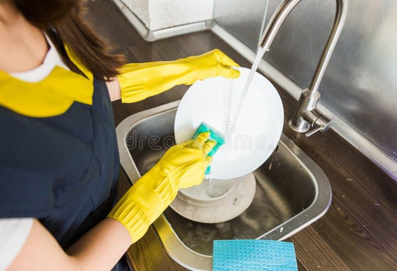 Uma jovem mulher em luvas amarelas lava pratos com uma esponja no dissipador Servi?o de limpeza profissional da casa fotografia de stock royalty free