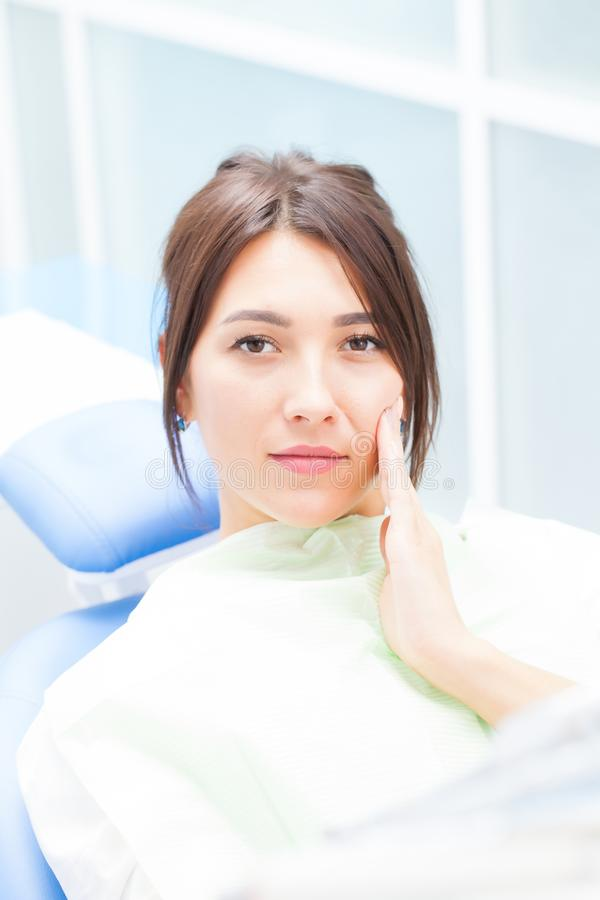 Uma jovem mulher em um dentista que se queixe da dor de dente fotos de stock