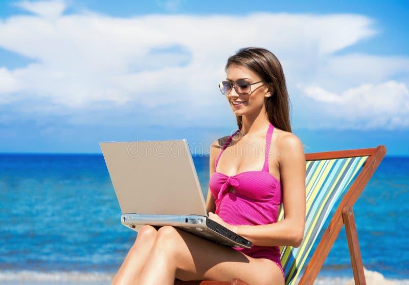 Uma jovem mulher em um roupa de banho cor-de-rosa com um computador na praia foto de stock royalty free