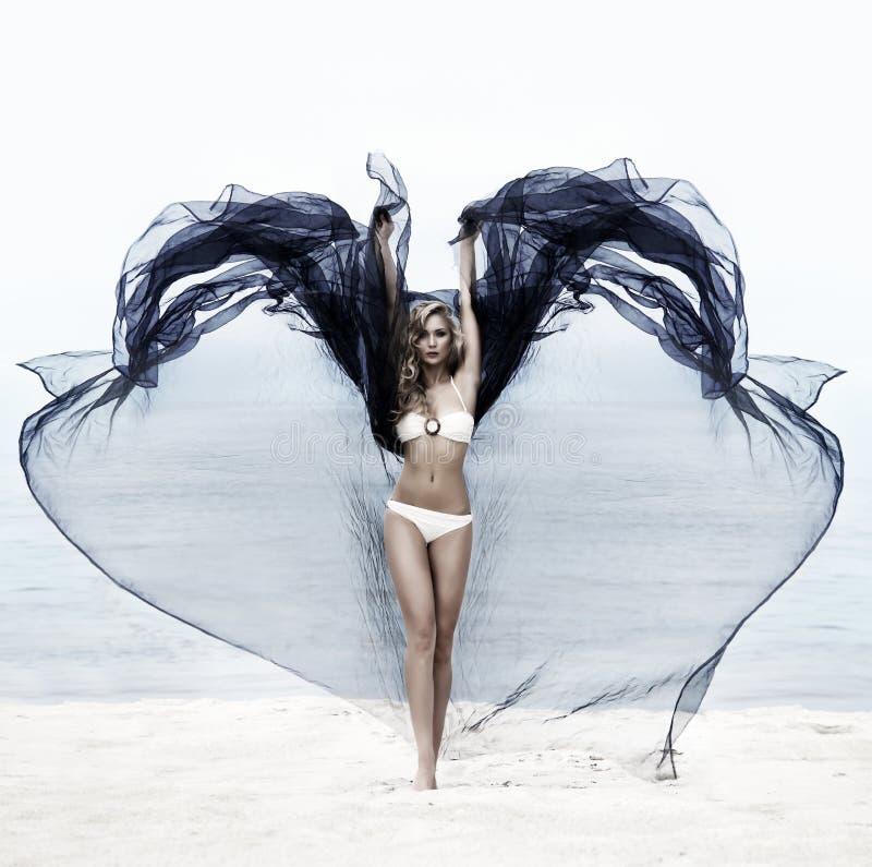 Uma jovem mulher em um roupa de banho na praia imagens de stock