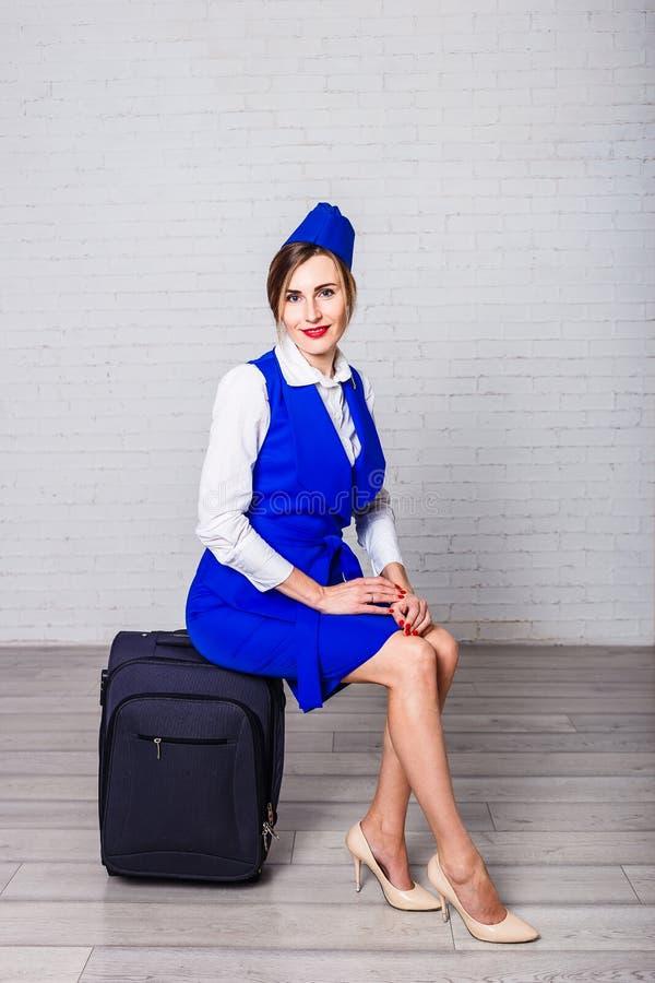 Uma jovem mulher em um terno azul que senta-se na mala de viagem foto de stock royalty free
