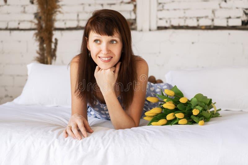 Uma jovem mulher em um vestido azul está encontrando-se na cama com um grande ramalhete de tulipas amarelas A menina sustenta seu imagens de stock