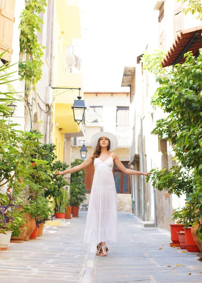 Uma jovem mulher em um vestido branco em umas férias imagens de stock