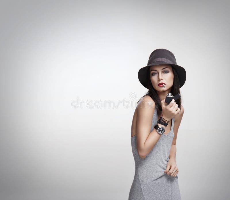 Uma jovem mulher em um vestido cinzento e em um chapéu imagens de stock