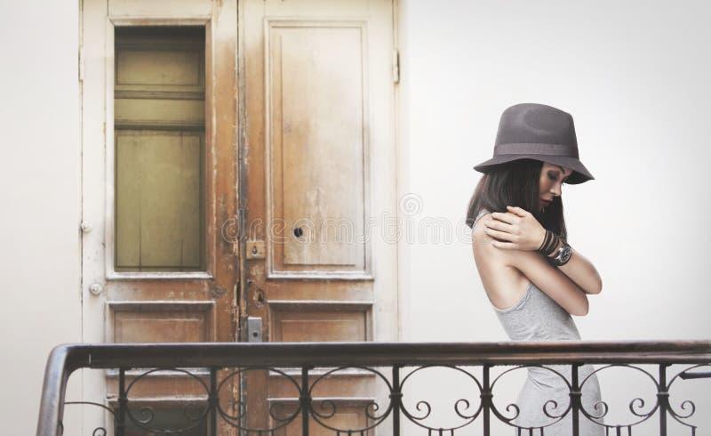 Uma jovem mulher em um vestido cinzento e em um chapéu fotografia de stock royalty free