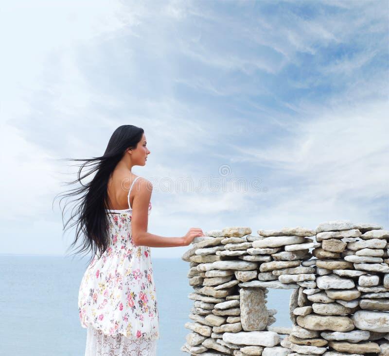 Uma jovem mulher em um vestido em um fundo do mar fotos de stock
