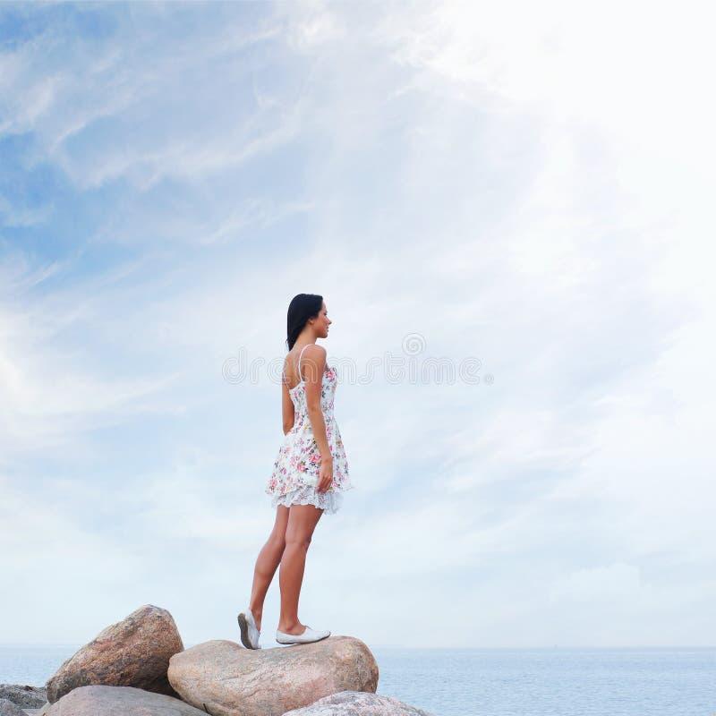 Uma jovem mulher em um vestido em um fundo do mar fotografia de stock royalty free