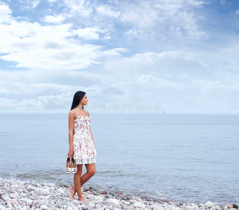 Uma jovem mulher em um vestido em um fundo do mar foto de stock