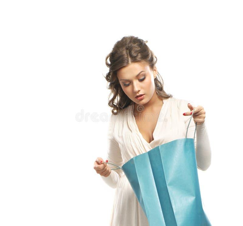 Uma jovem mulher em um vestido que abre um saco de compras foto de stock royalty free