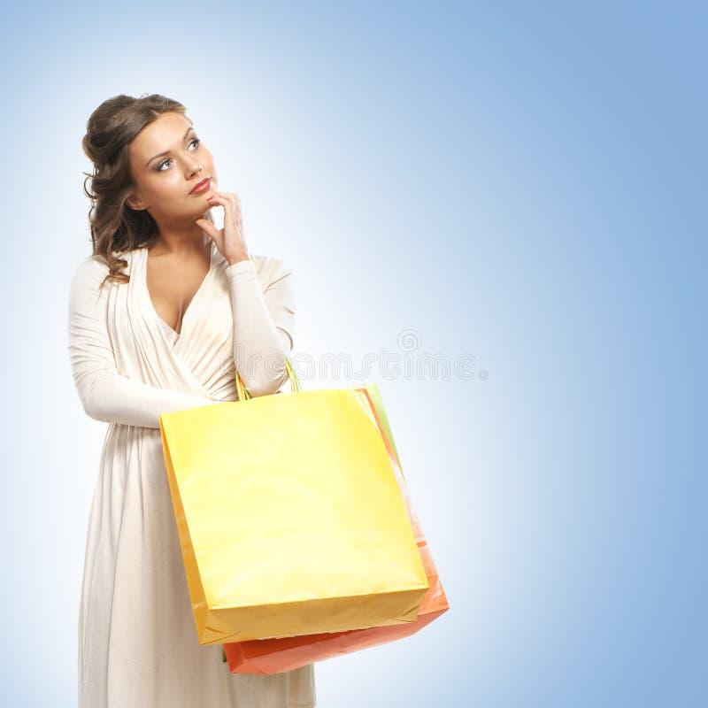 Uma jovem mulher em um vestido que guarda sacos de compras fotografia de stock