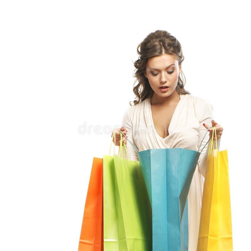 Uma jovem mulher em um vestido que guarda sacos de compras fotos de stock royalty free