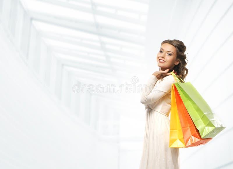 Uma jovem mulher em um vestido que guardara sacos de compras fotografia de stock