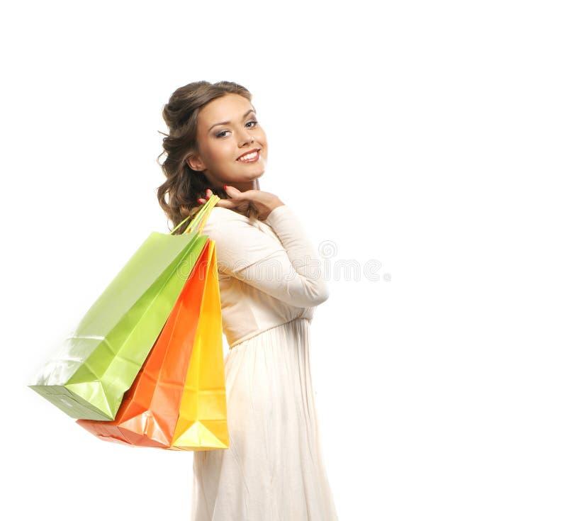 Uma jovem mulher em um vestido que guardara sacos de compras fotos de stock royalty free