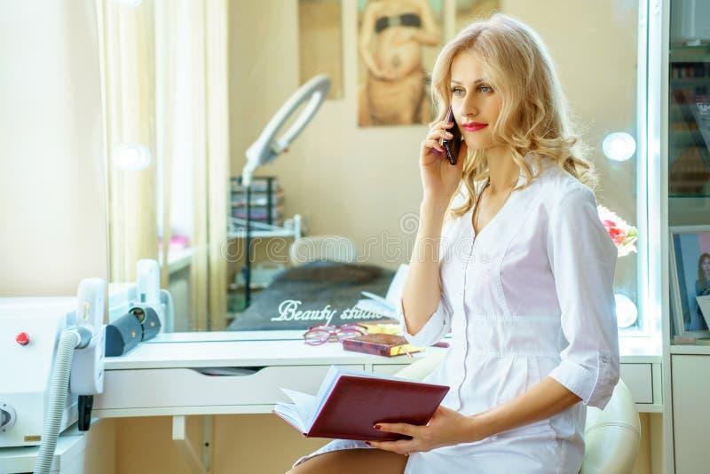 Uma jovem mulher em uma veste branca que chama o telefone no escritório de um esteticista imagem de stock royalty free