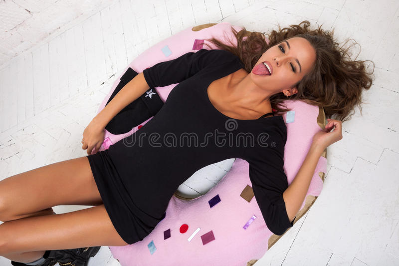 Uma jovem mulher encontra-se em uma filhós e língua mostrar Parede de tijolo branca, não isolada foto de stock