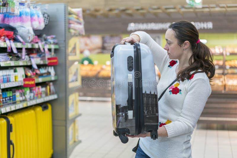 Uma jovem mulher escolhe uma mala de viagem para viajar na alameda imagens de stock
