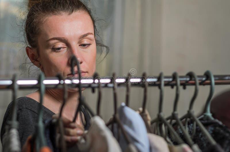 Uma jovem mulher escolhe a roupa em ganchos durante a compra fotos de stock royalty free