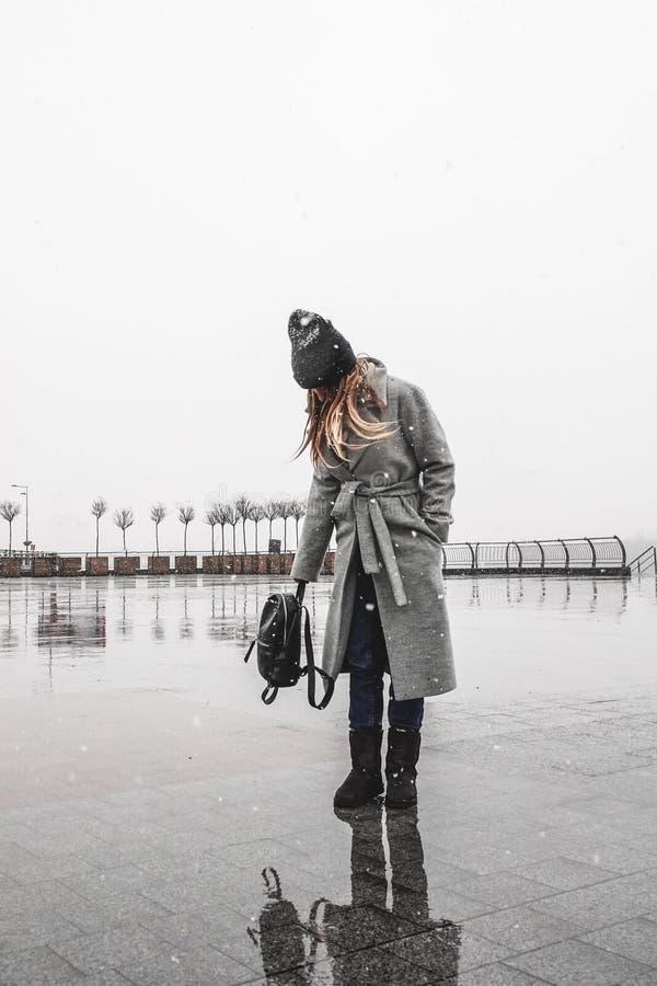 Uma jovem mulher está andando na neve na cidade fotografia de stock royalty free