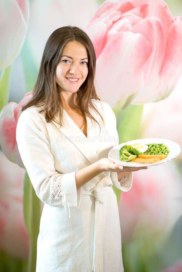 Uma jovem mulher está guardando uma placa de vegetais fervidos Propaganda da nutrição apropriada foto de stock