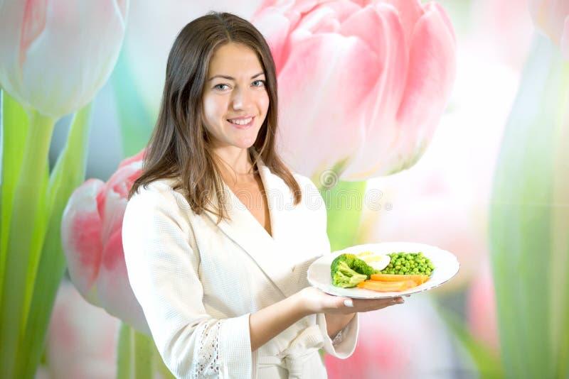 Uma jovem mulher está guardando uma placa de vegetais fervidos Propaganda da nutrição apropriada imagens de stock royalty free